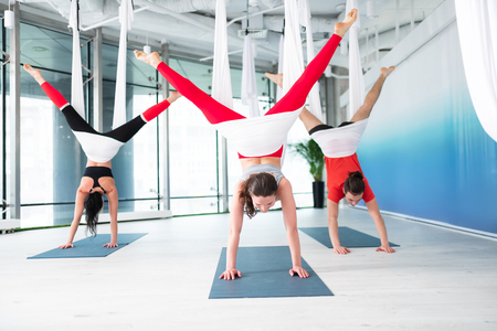 Standing on arms. Three active and fit people standing on their arms while doing aerial yoga