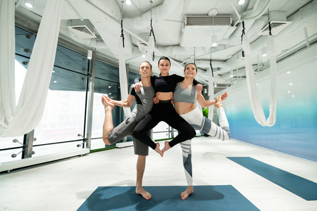 Friend in air. Man and woman holding their slim friend in the air while practicing yoga