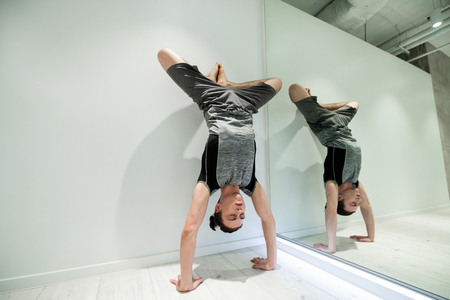 Stand near wall. Dark-haired man wearing grey shorts and t-shirt doing arm stand near wall and mirror