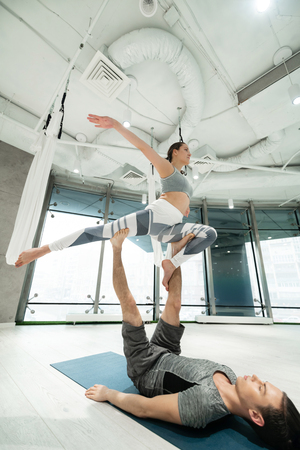 Strong sport couple. Strong sport couple feeling amazing while practicing fitness yoga in spacious room