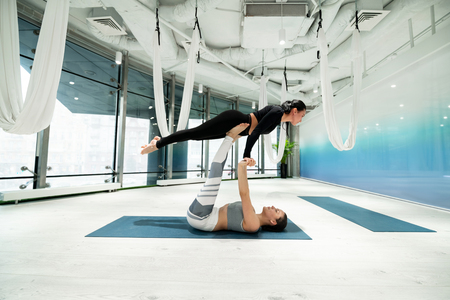 Strong women. Two strong and fit women wearing leggings practicing fitness yoga together