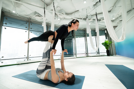 Student on legs. Yoga trainer holding her student on arms and legs while practicing fitness yoga together