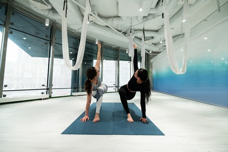 Yoga on mats. Two fit women with ponytails wearing leggings while doing yoga on sport mats together