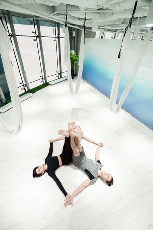 Calming bodies. Top view of women and man calming their bodies lying on floor after aerial yoga