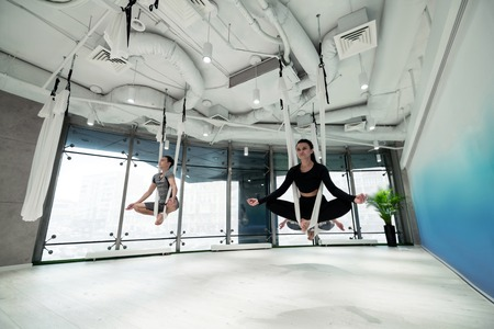 Doing flying yoga. Women and man wearing sport clothes feeling amazing while doing flying yoga