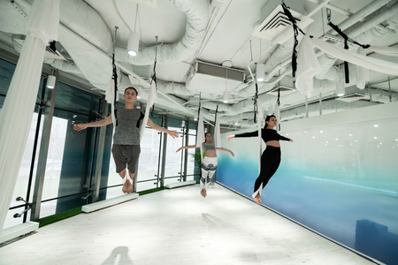 Antigravity yoga. Man and two women wearing sport clothes feeling free while practicing antigravity yoga