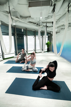 Yoga time. Top view of two women and man doing yoga on sport mats together