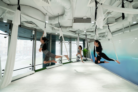 Practicing flying yoga. Dark-haired man and two women practicing flying yoga in spacious fitness center 版權商用圖片