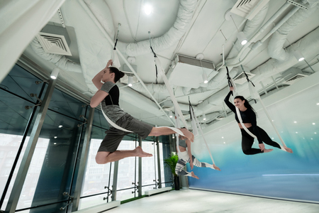Joining his friends. Dark-haired man joining his friends practicing antigravity yoga at the weekend 版權商用圖片