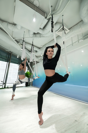 Sisters doing yoga. Dark-haired slim and fit sisters meeting and doing aerial yoga together