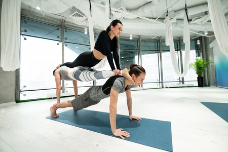 Women on back. Strong man holding two slim and fit women on his back while practicing fitness yoga