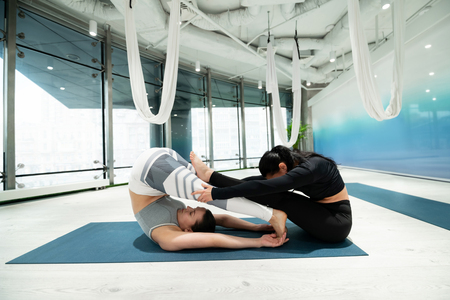 Improving flexibility. Two slim and fit women improving their flexibility while practicing yoga together