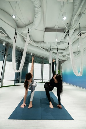 Weekend yoga. Two dark-haired sisters feeling amazing while doing yoga together at the weekend