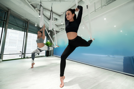 Leggings and tops. Two slim women wearing leggings and tops doing aerial yoga at the weekend