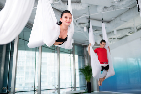 Yoga after work. Dark-haired woman feeling motivated while attending aerial yoga after work