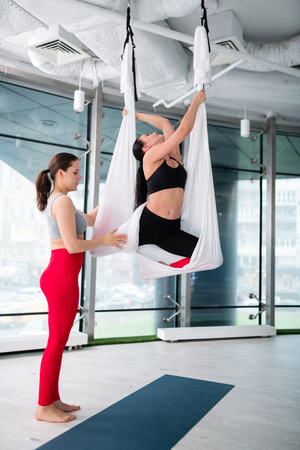 Helping student. Dark-haired yoga trainer in red leggings helping her student trying aerial yoga