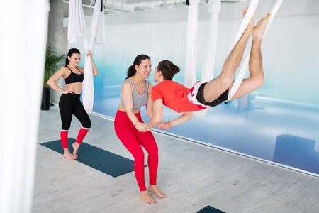 Trying new pose. Beautiful dark-haired trainer in red leggings assisting man trying new aerial yoga pose