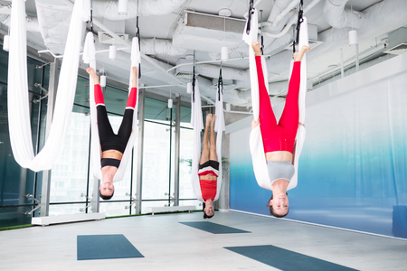 Professional poses. Two active and slim women and man doing professional poses practicing aerial yoga