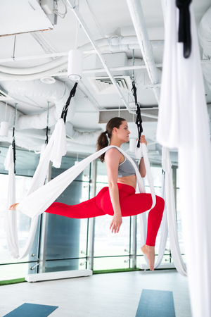 Leggings and top. Active woman wearing leggings and top doing flying yoga at the weekend Фото со стока
