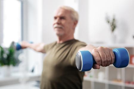 Attrezzatura sportiva. Messa a fuoco selettiva di un manubrio in una mano maschile durante l'allenamento