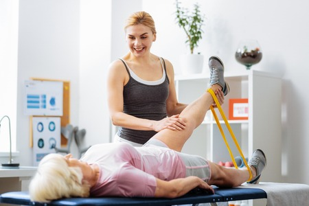 Physical therapy. Pleasant cheerful woman smiling to her patient while lifting her hand up