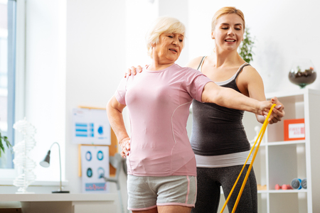 Professional help. Nice female coach standing behind her patient while helping her to do the exercise