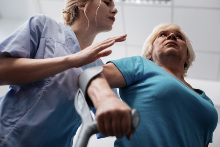 Problem with walking. Low angle of a sad aged woman using crutches while having problems with walking