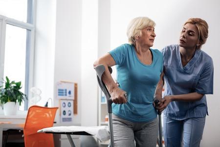 Ne t'inquiète pas. Belle infirmière agréable debout près de ses patients tout en l'aidant à marcher