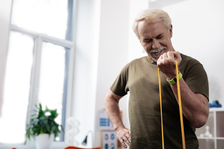 Sports equipment. Joyful strong man stretching his arm with a rubber band while training