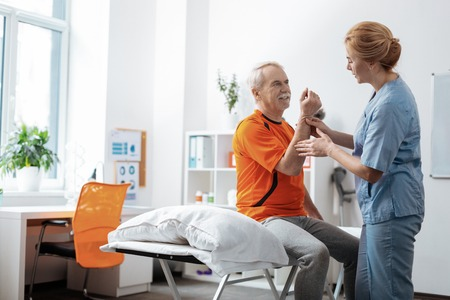 Healthcare center. Nice elderly man sitting on the medical bed while having his hand massaged