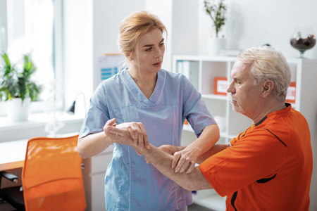 At work. Pleasant female nurse looking at her patient while massaging his hand