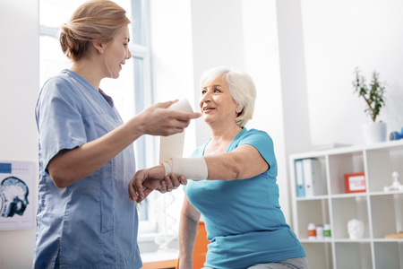 Elastic bandage. Pleasant delighted nurse looking at her patient while holding a white bandage 版權商用圖片