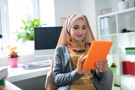 Woman reading. Appealing Muslim woman wearing hijab reading e-book feeling joyful
