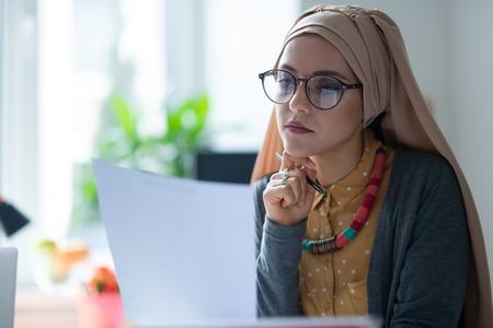 Young woman. Beautiful young woman wearing hijab and glasses feeling tired after working