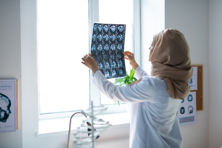 Looking at x-ray. Professional experienced doctor wearing hijab looking at x-ray standing near window Stockfoto