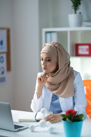 Overloaded with work. Female chemist wearing headscarf feeling overloaded with work after checking schedule