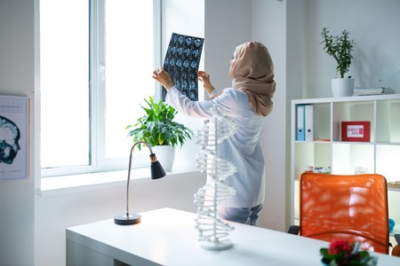 Near working table. Female medical scientist wearing headscarf standing near working table and looking at x-ray