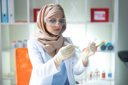 Young female chemist. Young female chemist headscarf and wearing white gloves holding test tubes Stockfoto
