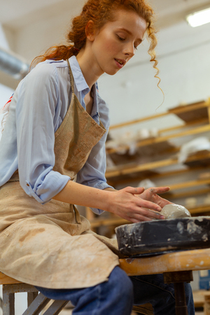 Hard-working lady. Focused young lady enjoying time spending in pottery workshop and dealing with professional equipment