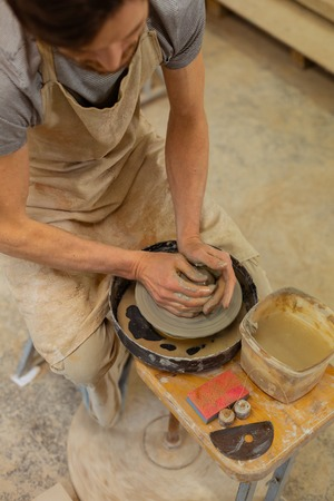 Clay with water. Hard-working skilled guy sitting on a wooden bench with pottery wheel and dealing with wet clay