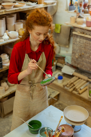 Covering piece. Attentive ginger girl in red shirt holding plate and paintbrush while working in pottery studio
