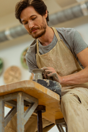 Showing his skills. Short-haired focused guy in apron carving elegant figures from wet clay on professional wheel