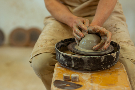 Manufacturing new pots. Qualified strong man with wet dirty hands producing on pottery wheel while staying in studio