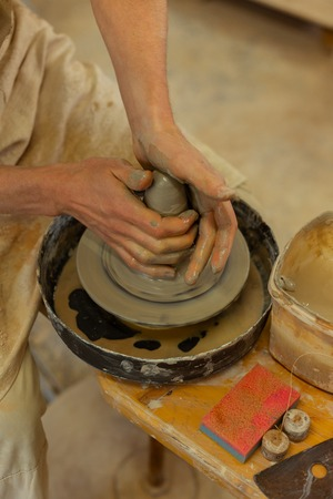 Forming new creation. Accurate professional pottery master using wheel in studio while making pot from wet clay Stock Photo - 123664157