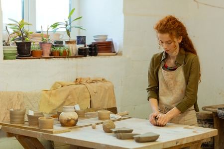 Creating needed form. Concentrated long-haired ginger girl intensely warming fresh clay while staying in equipped pottery workshop