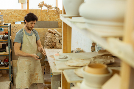 Starting work. Concentrated dark-haired guy in long apron rolling clay between two hands