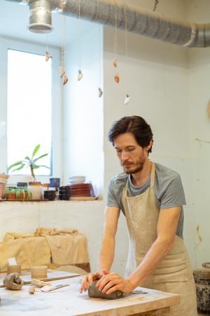 Good-looking pottery workshop. Focused peaceful dark-haired man rubbing piece of wet clay while staying in bright studio