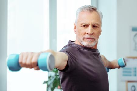 Starker Körper. Starker, gut gebauter Mann, der sein Training genießt und gleichzeitig einen starken Körper haben möchte