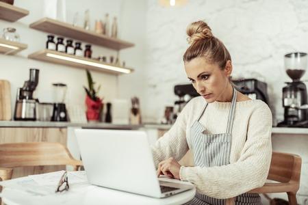 Endroit de travail. Propriétaire d'un café intelligent concentré assis à la table travaillant sur son ordinateur portable. Banque d'images