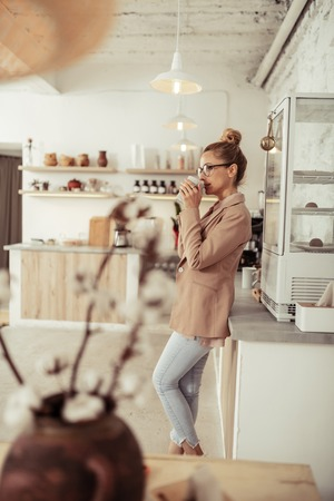 Enjoying free time. Smart smiling woman standing in the kitchen and drinking coffee during her coffee break.